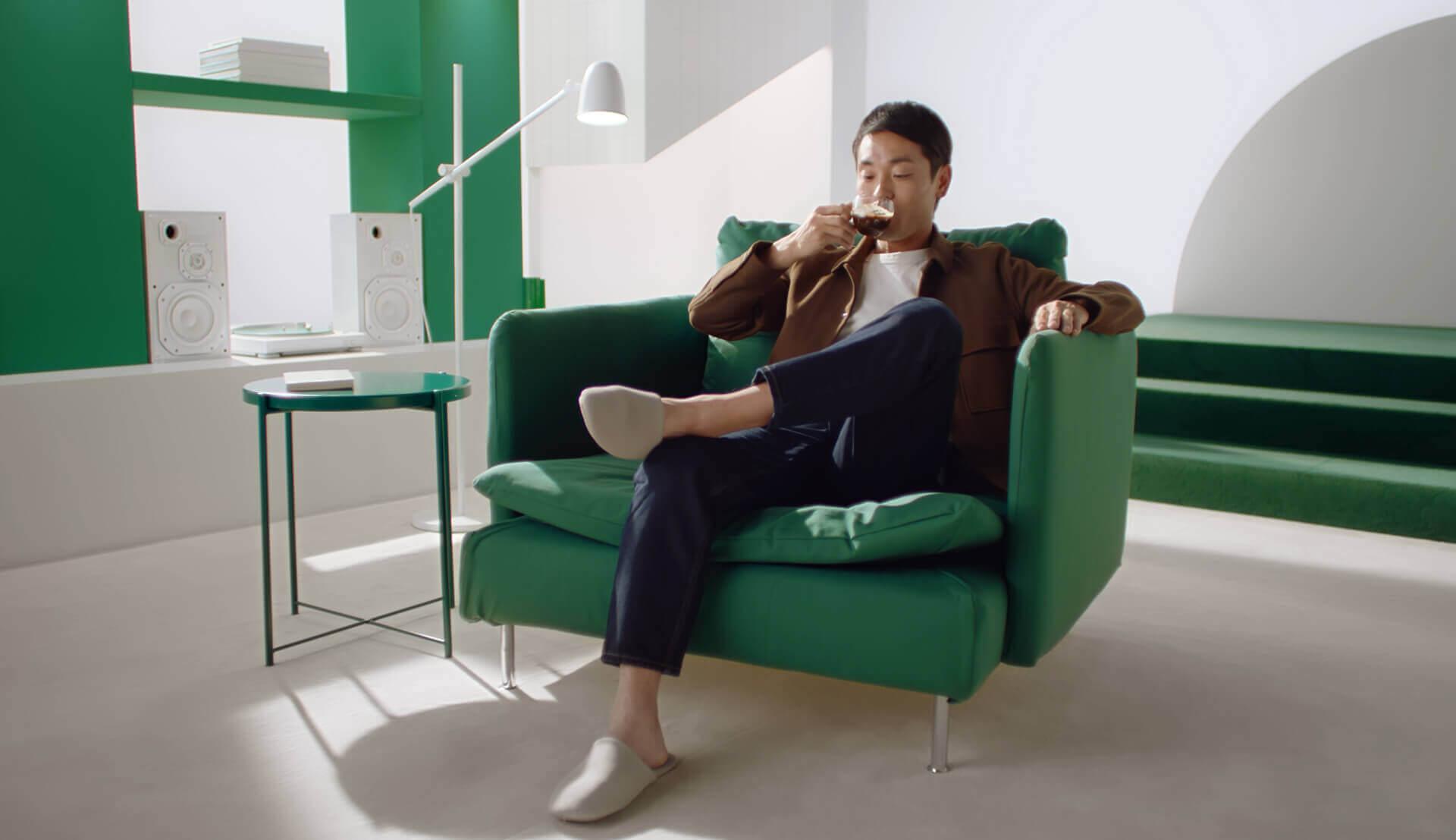 Mann sitzt mit Kaffee im Sessel