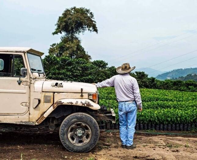 Kaffeebauer an Jeep angelehnt